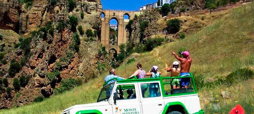 coche todoterreno con gente de pie parado observando un acueducto al fondo