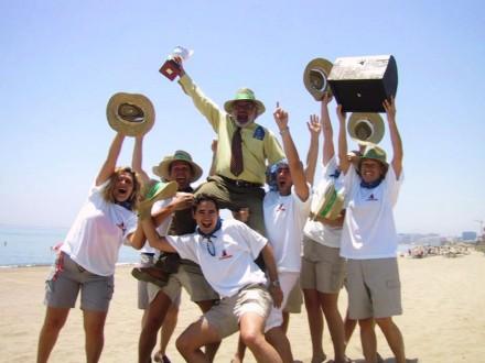 grupo de personas en la playa con trofeos y cajas con los brazos arriba